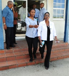 CEO and Publisher of the Nation newspaper, Vivian-Anne Gittens (right)  being led away by a police officer after being charged.  At left is Editor Emeritus Harold Hoyte who is also chairman of The Nation Publishing Co. Limited.
