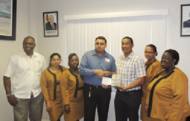 Finance Officer, Latchman Kumar hands over a cheque to co-founder of the K&S Organization, Kashif Muhammad while in the presence of fellow employees and Aubrey 'Shanghai' Major.