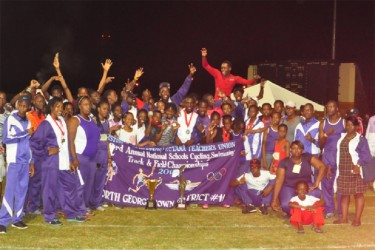 Athletes and officials of North Georgetown celebrating with their Champion-of- Champions trophy. (Orlando Charles photo)