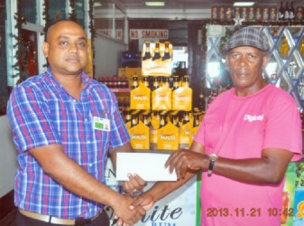 Coach Randolph Roberts of the Flying Ace Cycle Club of Berbice collects the sponsorship cheque from Banks DIH Limited Berbice Sales Manager Joshua Torrezao