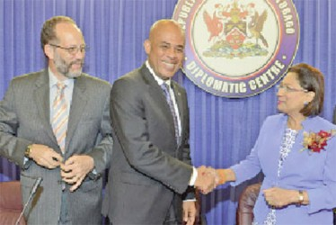 Caricom chairman Prime Minister Kamla Persad-Bissessar, right, greets Haitian President Michel Martelly during a special meeting of Caricom at the Diplomatic Centre, St Ann's, Port of Spain, yesterday