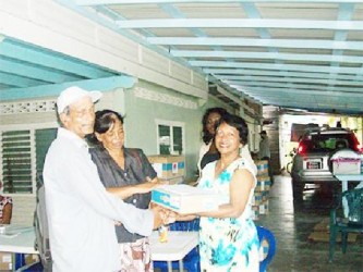 Member of Parliament Indranie Chandarpal handing over a laptop to one of the recipients at the One Laptop Per Family (OLPF) distribution exercise All Stars Sports Club, Supply, Mahaica. (Government Information Agency photo)