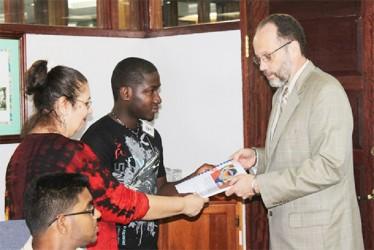 Marchenson Desrosier (centre), a Haitian student at the University of Guyana and Danuta Radzik (left), presents the petition to Secretary-General Irwin LaRocque.