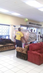 Employees at Courts fetching new stock into the store after appliances and furniture on the ground floor was damaged by flood waters on Wednesday.