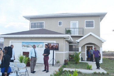 CEO Windsor Estates Danny Sawh and Prime Minister Samuel Hinds, standing in front of the company's model home. (Government Information Agency photo)
