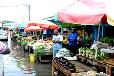 Making do: Vending above the flood at Bourda Market on Wednesday