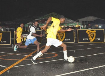 Christopher Darlington of California Square (right) in the process of attacking the Kingston goal with his (left) defensive marker in hot pursuit