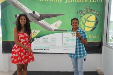 Fly Jamaica representative Susan Razack (right) presents a replica boarding pass to Go-Kart driver Emma Vieira, who won a round trip ticket to Jamaica.