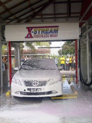 Prime Minister Samuel Hinds on Saturday officially opened the Xstream Clean Cars Complex on South Road, Georgetown, following which his car was the first to receive a wash.  This GINA photo shows Prime Minister Samuel Hinds' car getting the first wash at the Xstream Clean Cars Complex while he sits inside the vehicle.