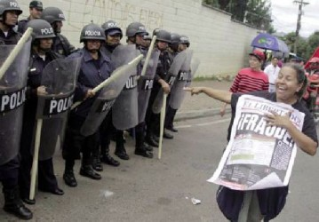 A supporter of Xiomara Castro, presidential candidate of the Liberty and Refoundation party (LIBRE), laughs and points as she holds up a poster with the word ''Fraud'' written on it, as she demonstrates next to riot police officers standing guard during a protest against the results of the presidential election in Tegucigalpa December 1, 2013. (Reuters/Jorge Cabrera)