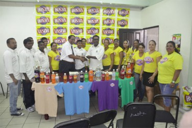 Guyana Beverage Company Incorporated president Robert Selman presents a cheque to the President of the Enterprise Busta Sports Club, Karran Ramdhoon while Busta representatives and club officials look on.