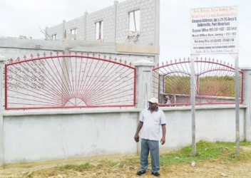 Pandit Dhanesar stands in front of the building