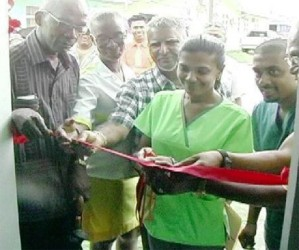 Dr. Renika Veerasammy being assisted to cut the ribbon the declare the  diabetic foot clinic open