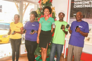 Head of Marketing at Digicel Guyana Jacqueline James (centre) stands among Digicel customers while showcasing some of the handsets on sale as part of the company's Christmas promotion.
