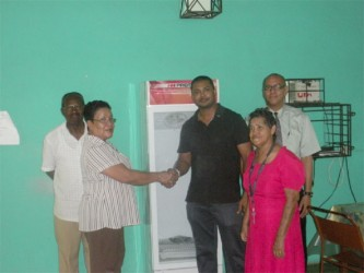 Norma Hamilton (second from left), Administrator of Uncle Eddie's Home shakes hands with  Leader of Harmony Lodge Azad De Abreu during yesterday's donation, while Gladwyn Anderson, VP of the Home's Management Committee (at left), lodge member Neil D'Ornellas (in background at right) and a resident of the Home look on.