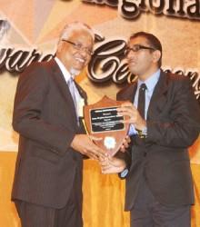 Nigel Harris presenting Anna Regina Secondary School Principal Lalljeet Ruplall receiving the 2013 CSEC school of the year award