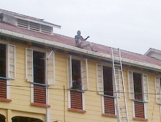 Delon King sits on the gutter of one of the Palms' buildings as he spoke to the institution's administrators