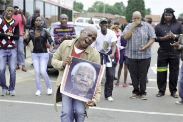 People sing and dance during a gathering of mourners on Vilakazi Street in Soweto, where the former South African President Nelson Mandela resided when he lived in the township, December 6, 2013. REUTERS/Ihsaan Haffejee