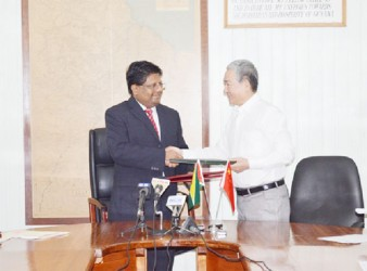 Finance Minister Dr Ashni Singh (left) and Chinese Ambassador to Guyana Zhang Limin exchanging documents.  (GINA photo)