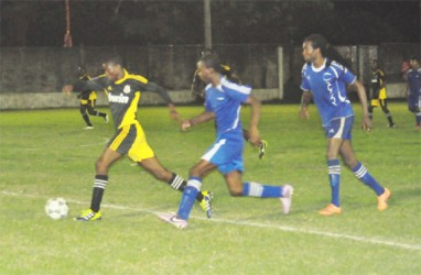 BV Triumph United's Akin Curry (centre) and Delroy Dean (right) in pursuit of a Grove Hi-Tech player.  (See story on page 27.)