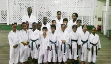 Sensei Winston Dunbar (left of standing row) posing with the successful students. Sadelle Britton is extreme right position in the front row.
