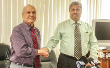Former DDL chairman Yesu Persaud (left) shakes the hand of the man appointed to take the company into the future, Komal Samaroo