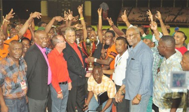 Slingerz FC captain Dwain Jacobs collecting the championship trophy from Banks DIH Limited Brand Executive Carlton João while members of the GFA, GFF, Banks DIH and Slingerz look on.