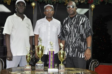 Secretary of the Georgetown Dominoes Association Mark Wiltshire (left), president of the USA Dominoes Federation George Abrams (centre) and PRO of the GDA Basil Bradshaw display the trophies.