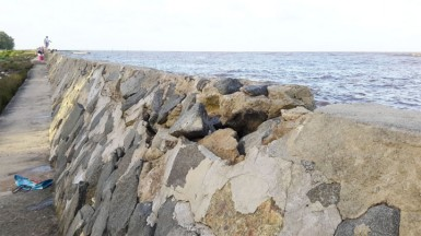 Boulders beginning to crumble at the top of the seawall.