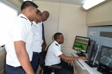 Guyana Revenue Authority (GRA) staffers monitoring scanner operation from the control room of the mobile scanner (GINA photo)