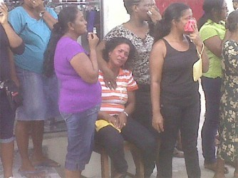 A distraught Jennifer Dyal (seated) Judith D'Oliviera's sister, being comforted by residents as the body was being removed yesterday.