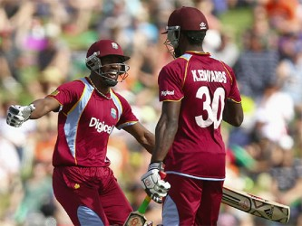 Century makers Dwayne Bravo, left and Kirk Edwards celebrate on the way to their team's whopping 2-3-run win over New Zealand yesterday in the fifth and final One Day International which ensured the West Indies a share of the series. (Cricket365 photo)