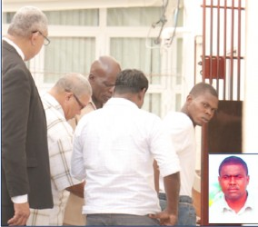 In this Arian Browne photo, prisoner Dellon Abrams is being escorted into the lock-ups at the Georgetown Magistrates' Court complex. Inset is slain Police Detective Corporal Seburn Elias.