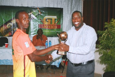 'Boney' Gittens receives the MVP trophy from Mortimer Stewart, Banks DIH Outdoor Events Manager.