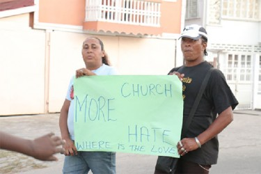 Two of the persons participating in the walk holding a placard.