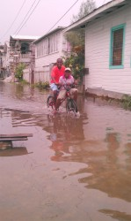 These two boys were taking a ride through James Street, Albouystown yesterday as floodwaters continued to rise in the area.