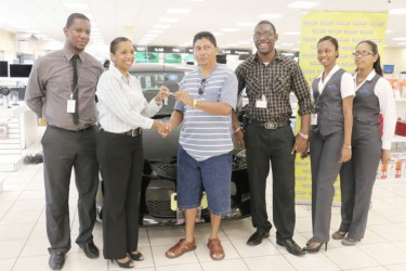 Enmore villager Francis Koo (third from left) as he receives the key to his new Mazda Demio car from Marketing Director of Courts Molly Rampersaud. With them are some of Courts' marketing staff.