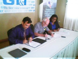 From left to right are GT&T CEO, Radha Krishna Sharma; President of THAG Kit Nascimento and GT&T Public Relations Officer Allison Parker, at the signing of the sponsorship agreement between GT&T and THAG.