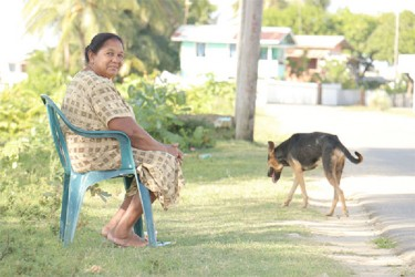 Mavis Deonarine sitting opposite her house in the scheme