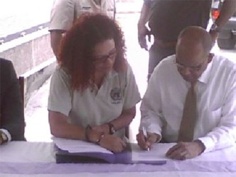 Juliet Solomon of UNLIREC and Home Affairs Minister Clement Rohee at the signing for the handover of the Hydraulic Shears and Small Arms and Ammunition Tank to Guyana.