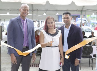 Subrina Sukhu (centre) cuts the ribbon, opening the new Digital Technology store on Brickdam. She is flanked by President of Georgetown Chamber of Commerce and Industry Clinton Urling (left) and her husband.