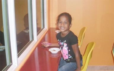A young girl enjoys her yogurt yesterday at the official opening of Yog Yog's Frozen Yogurt