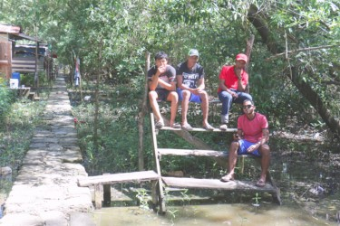 A group of young boys hanging out along the concrete walkway leading out to the river. The  pathway leads to a stone structure which the residents call the 'First Baby monument' at the end of the squatting area.