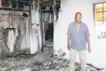 Shamlal Khodai stands in his damaged house