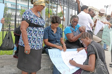 Some of the protesters near Parliament today condemning the police treatment of Colwyn Harding.  Harding has alleged that he was sodomized by a policeman with a baton and beaten among other indignities. He is now hospitalized at the Georgetown Hospital.