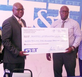 Chief Education Officer Olato Sam (left) receiving a cheque from GT&T Chief Financial Officer Justin Nedd for the Children's Costume Parade 2014.