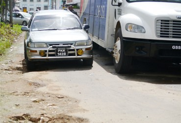 A vehicle trying to manoeuvre on the deplorable street where a truck is parked