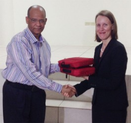 Minister of Home Affairs Clement Rohee (left) receives two of the 200 fraudulent document detection kits from Canadian High Commissioner Nicole Giles (right).