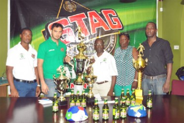 General Manager of the Slingerz FC, Colin 'BL' Aaron and Brand Manager of Stag, John Maikoo pose for a photo opportunity with the champion's trophy following the launch of yesterday's second annual West Side Stag/Mashramani Champion's Cup. Looking on are (from left), Vurlon Mills, Christine Schmidt and Rawle Toney. (Orlando Charles photo)