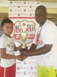 Ming Wong, skipper of the Kuru Kururu team receives the trophy from Guyana Cricket Board coordinator Andrew Alleyne.